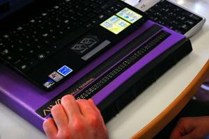 Un lecteur dont on voit la main lit un texte sur une plage braille reliée à un ordinateur portable