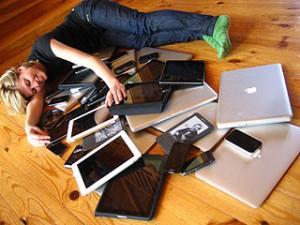 Jeune fille couchée au milieu d'une multitude d'outils informatiques (tablettes, PC, téléphones mobiles, liseuses)