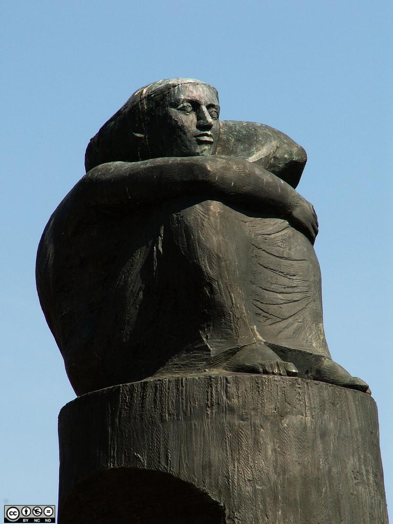 Statue de femme assise, les mains entourant ses genoux, regardant la mer.